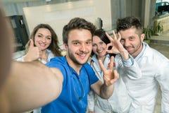 Усмехаясь команда докторов и медсестер на больнице принимая Selfie стоковая фотография rf