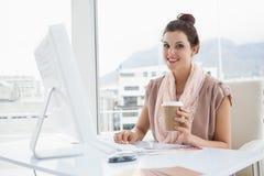 Усмехаясь коммерсантка держа бумажный стаканчик кофе Стоковая Фотография RF