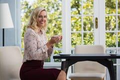 Усмехаясь коммерсантка держа кофейную чашку в кафе Стоковое Изображение RF