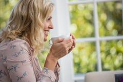 Усмехаясь коммерсантка держа кофейную чашку в кафе Стоковые Изображения RF