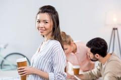Усмехаясь коммерсантка держа кофейную чашку с коллегами близко мимо Стоковые Изображения