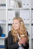 Усмехаясь коммерсантка держа кофейную чашку Стоковая Фотография RF