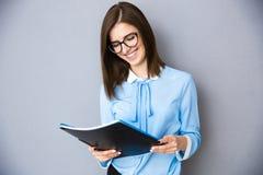 Усмехаясь коммерсантка держа папки над серой предпосылкой Стоковые Фото