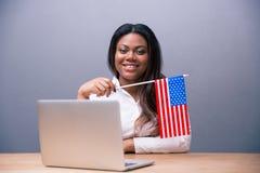 Усмехаясь коммерсантка держа флаг США стоковые фото