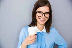 Усмехаясь коммерсантка держа чашку с кофе Стоковое Изображение