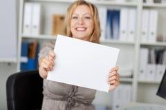 Усмехаясь коммерсантка держа чистый лист бумаги Стоковые Фото