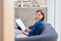 Усмехаясь коммерсантка на кресле офиса с обработкой документов Стоковое Изображение RF