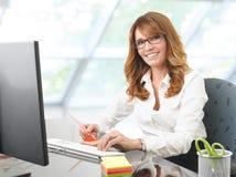 Усмехаясь коммерсантка на столе офиса с компьютером Стоковое фото RF