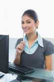 Усмехаясь коммерсантка сидя на столе офиса Стоковые Фотографии RF