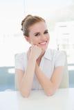 Усмехаясь коммерсантка сидя на столе офиса Стоковое Фото