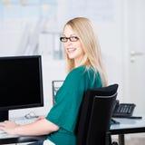 Усмехаясь коммерсантка сидя перед компьютером Стоковое Изображение