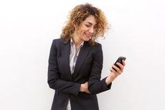 Усмехаясь коммерсантка смотря мобильный телефон Стоковые Фотографии RF