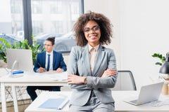 Усмехаясь коммерсантка стоя в офисе с ее мужским сотрудником таблицей стоковое фото
