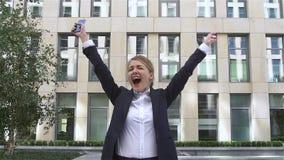 Усмехаясь коммерсантка с руками вверх очень эмоциональная блондинка, замедленное движение видеоматериал