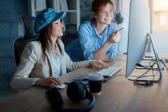 Усмехаясь коммерсантки обсуждая на работе офис-дизайнеров Стоковое Фото