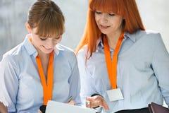 Усмехаясь коммерсантки обсуждая над документами в офисе Стоковая Фотография RF