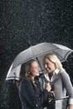 Усмехаясь коммерсантки под одним зонтиком в дожде Стоковое Изображение RF