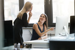2 усмехаясь коммерсантки работая с компьютером совместно Стоковое Изображение RF