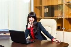 Усмехаясь коммерсантки сидя на таблице в офисе Стоковые Изображения RF