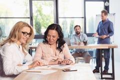 Усмехаясь коммерсантки сидя на таблице и работая совместно в офисе Стоковые Изображения