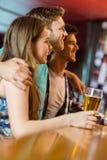 Усмехаясь коричневые волосы стоя с рукой вокруг его друзей Стоковая Фотография