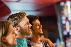 Усмехаясь коричневые волосы стоя с рукой вокруг его друзей Стоковая Фотография RF