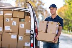 Усмехаясь коробки работника доставляющего покупки на дом нагружая в его тележку стоковое изображение