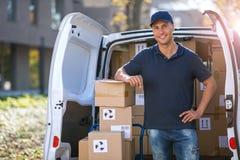 Усмехаясь коробки работника доставляющего покупки на дом нагружая в его тележку стоковые фотографии rf