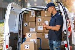 Усмехаясь коробки работника доставляющего покупки на дом нагружая в его тележку стоковое фото rf