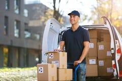 Усмехаясь коробки работника доставляющего покупки на дом нагружая в его тележку стоковые изображения rf