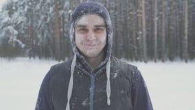 Усмехаясь, который замерли человек в снеге смотря камеру в лесе зимы после невосприимчивости и холода шторма снега Стоковые Фото