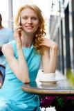 Усмехаясь кофе девушки выпивая в кафе и говорить на smartphone Стоковые Фотографии RF