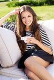 Усмехаясь кофе женщины выпивая в кафе Стоковое Изображение