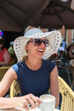 Усмехаясь кофе женщины выпивая на кафе улицы Стоковое Изображение RF