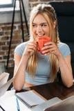 Усмехаясь кофе кавказской женщины выпивая пока сидящ на таблице Стоковое Фото