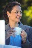 Усмехаясь кофе коммерсантки выпивая с компьтер-книжкой Стоковые Изображения RF