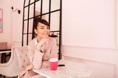 Усмехаясь кофе милой девушки выпивая пока сидящ на столовой Стоковые Фотографии RF