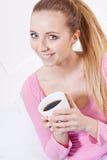 Усмехаясь кофе молодой белокурой женщины выпивая Стоковое Изображение RF