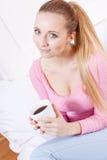Усмехаясь кофе молодой белокурой женщины выпивая Стоковые Фотографии RF