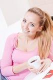 Усмехаясь кофе молодой белокурой женщины выпивая Стоковые Изображения RF