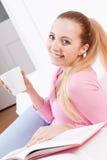 Усмехаясь кофе молодой белокурой женщины выпивая Стоковое Изображение
