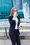 Усмехаясь кофе молодой женщины выпивая перед деловым центром Стоковые Фотографии RF