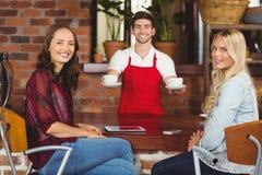 Усмехаясь кофе сервировки кельнера к клиентам Стоковые Фотографии RF