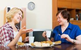 Усмехаясь коллеги выпивая coffe и беседуя во время перерыва для Стоковое фото RF