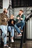Усмехаясь коллеги в офисе говоря друг с другом Стоковое Изображение