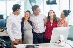 Усмехаясь коллеги дела взаимодействуя друг с другом на столе Стоковое Фото
