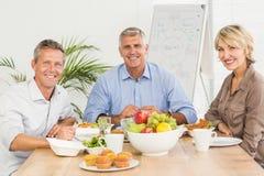 Усмехаясь коллеги дела имея обед совместно Стоковое фото RF