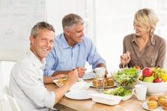 Усмехаясь коллеги дела имея обед совместно Стоковое Фото