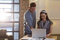 Усмехаясь коллеги используя компьтер-книжку в офисе Стоковое Фото