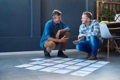 2 усмехаясь коллеги коллективно обсуждать с бумагами на поле офиса Стоковое Изображение